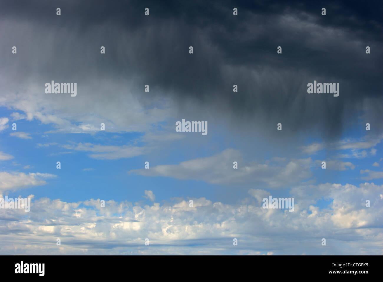 Rain falling from Cumulonimbus clouds over the sea - Stock Image