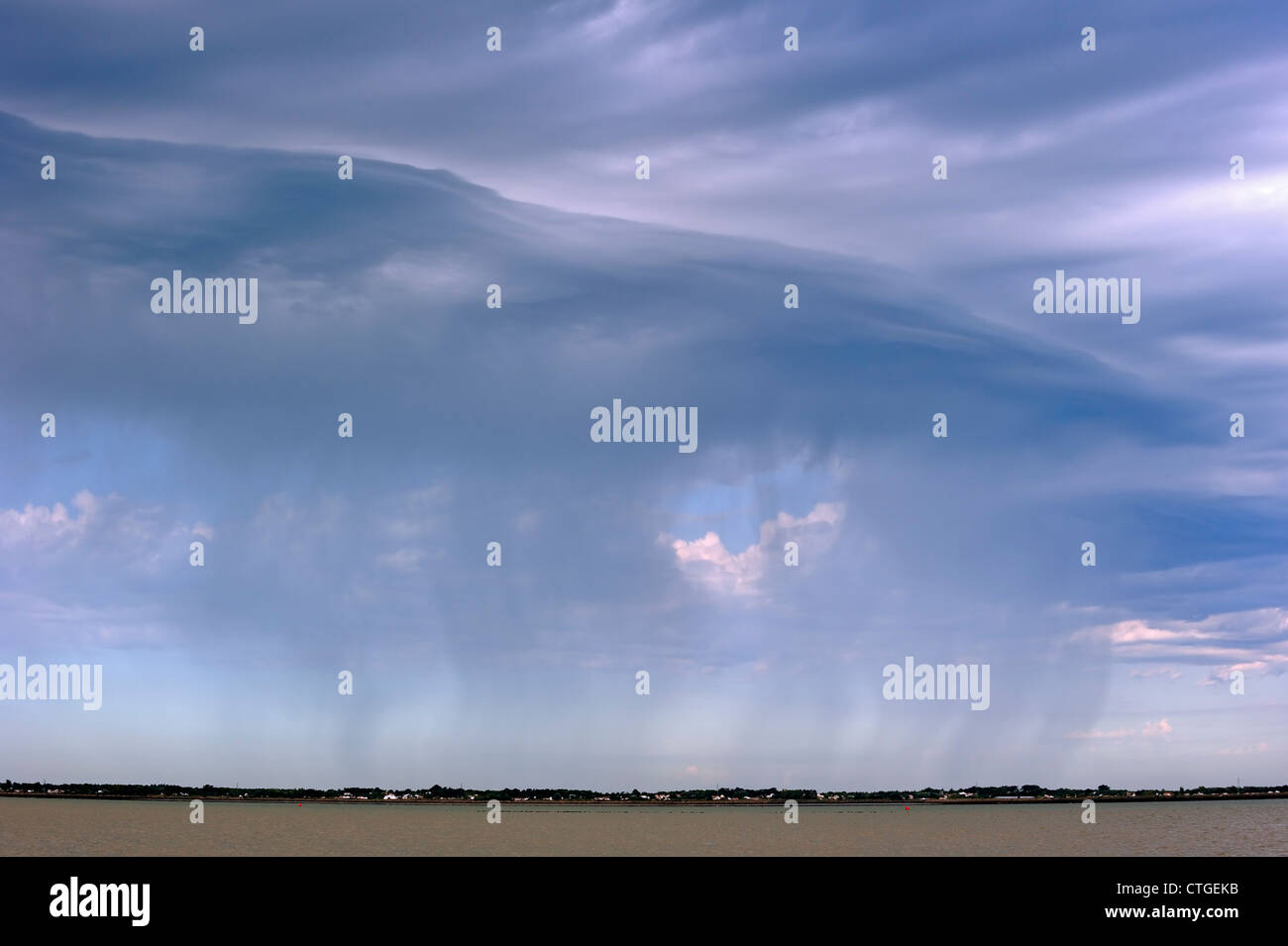 Cumulonimbus praecipitatio cloud causing rainfall over sea - Stock Image