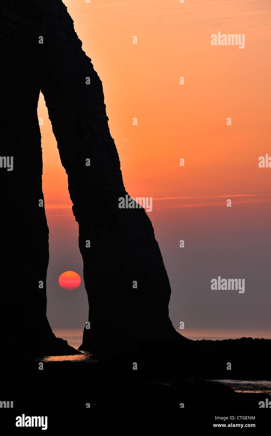 Silhouette of the Porte D'Aval, a natural arch in the chalk cliffs at Etretat at sunset, Côte d'Albâtre, - Stock Image