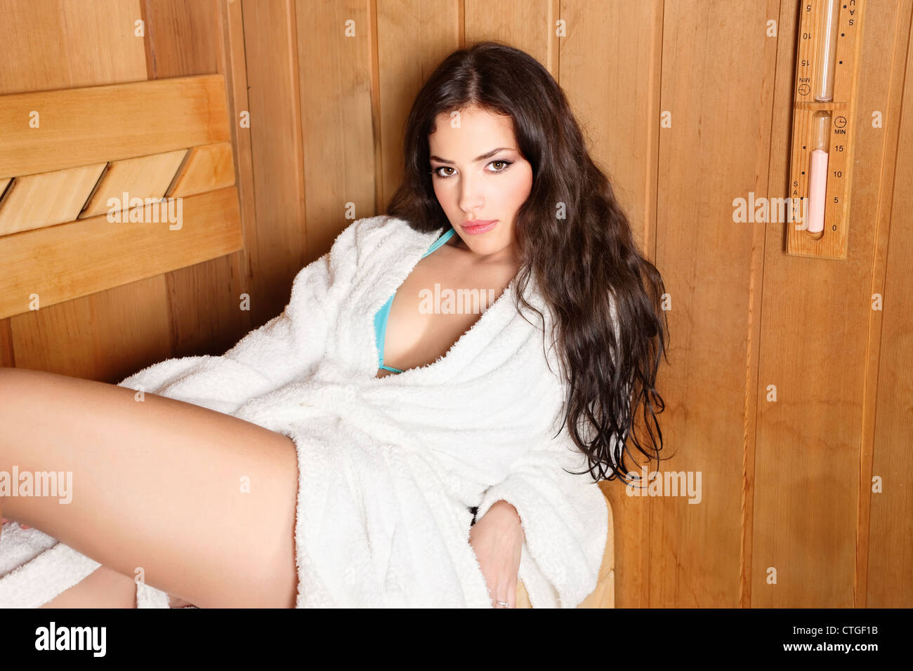 young woman relaxing in finnish type wooden sauna - Stock Image