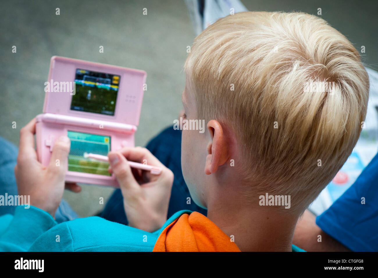 London St Pancras Station young blond boy lad playing football game on Nintendo DS games console in pink on lower - Stock Image