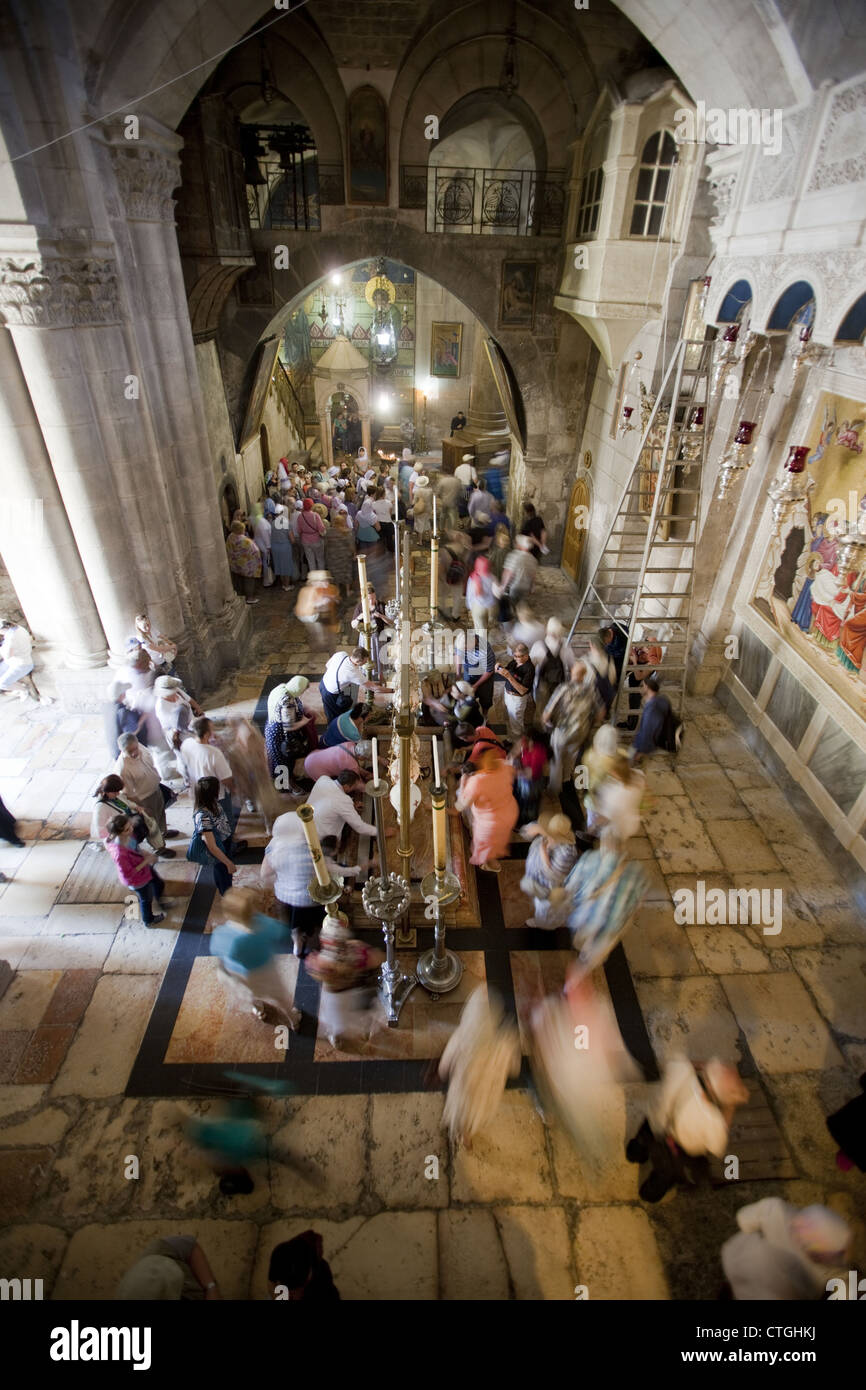 Religious pilgrims and tourists around the Stone of Anointing in the Church of the Holy Sepulchre, Jerusalem, Israel Stock Photo