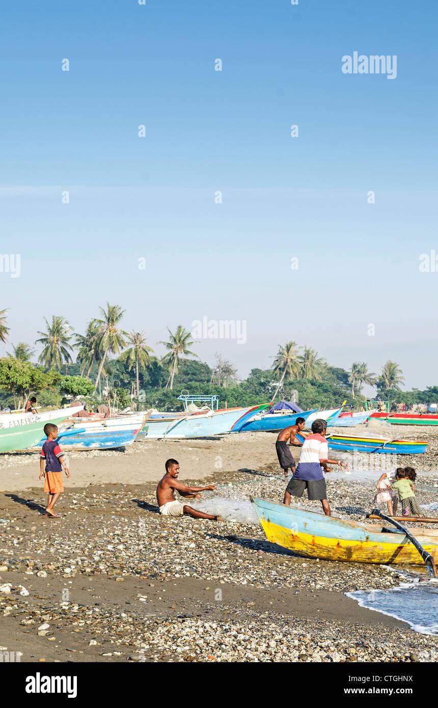 fishermen working on beach in dili east timor - Stock Image