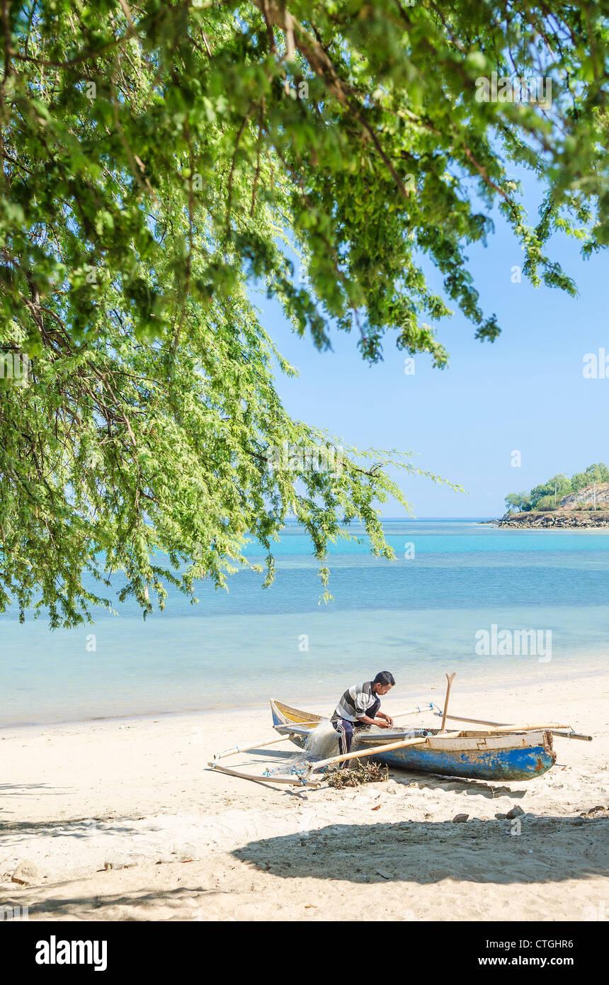 fisherman working on beach in dili east timor - Stock Image