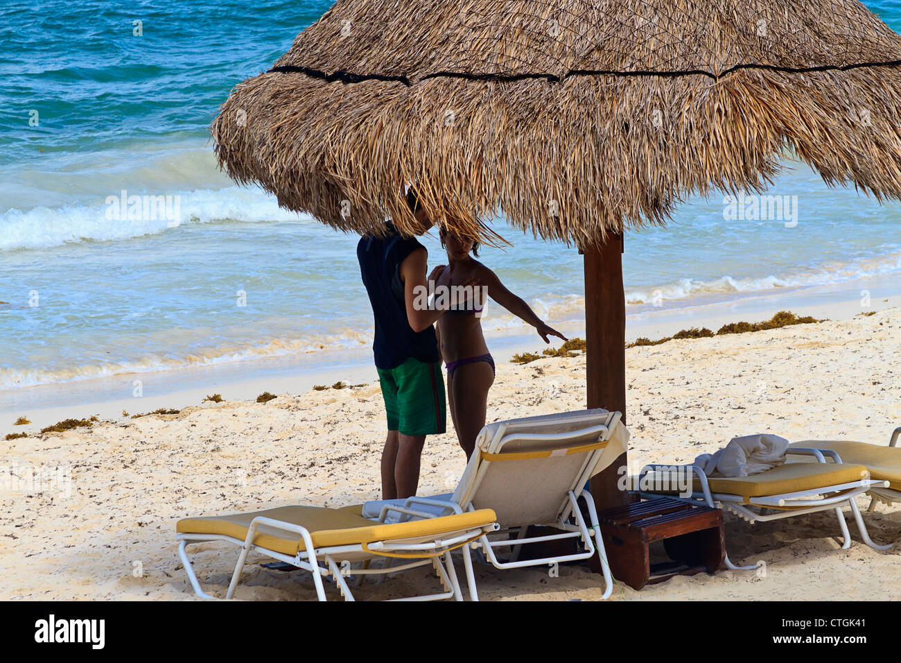 Couple on beach along Riviera Maya, Yucatan, Mexico. Caribbean ocean is behind them as they stand beneath a palm - Stock Image