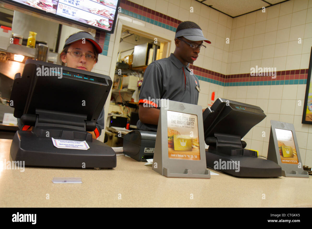 Port St. Lucie Florida Burger King fast food restaurant counter cashier woman Black man job service uniform - Stock Image