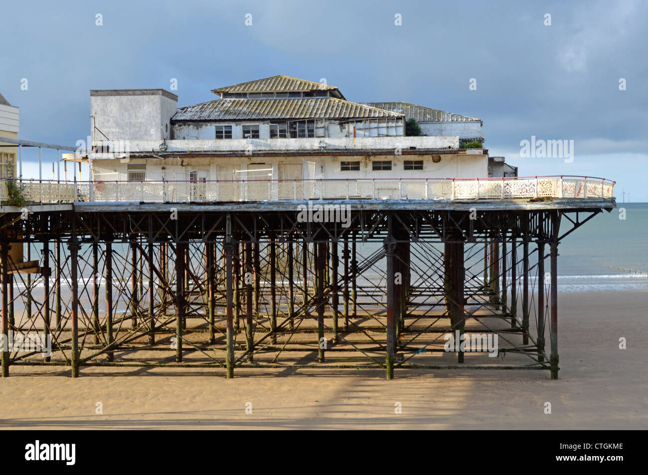 The decaying Victoria Pier on the beach at Colwyn Bay - Stock Image