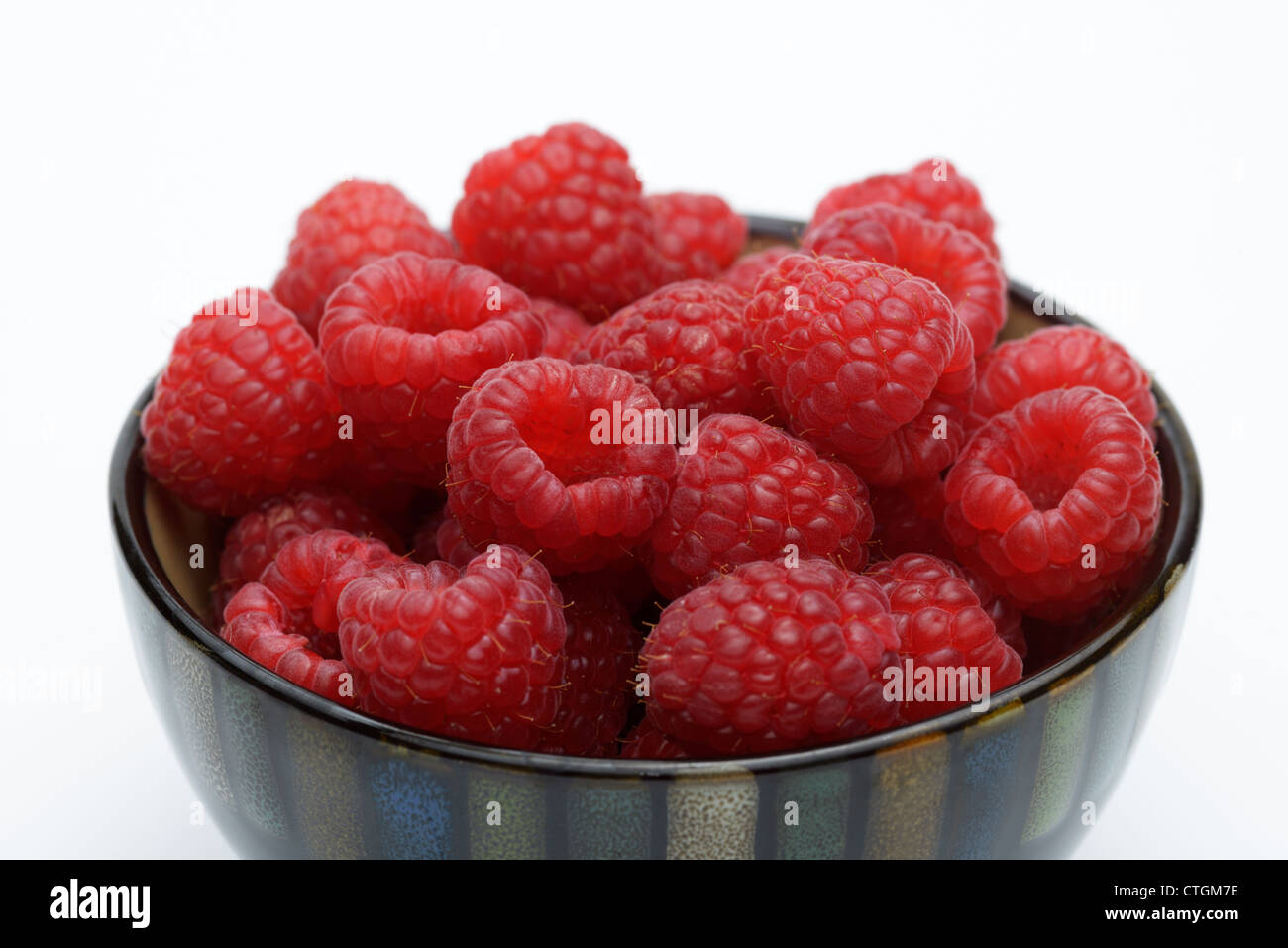Fresh raspberries in a bowl, close-up - Stock Image