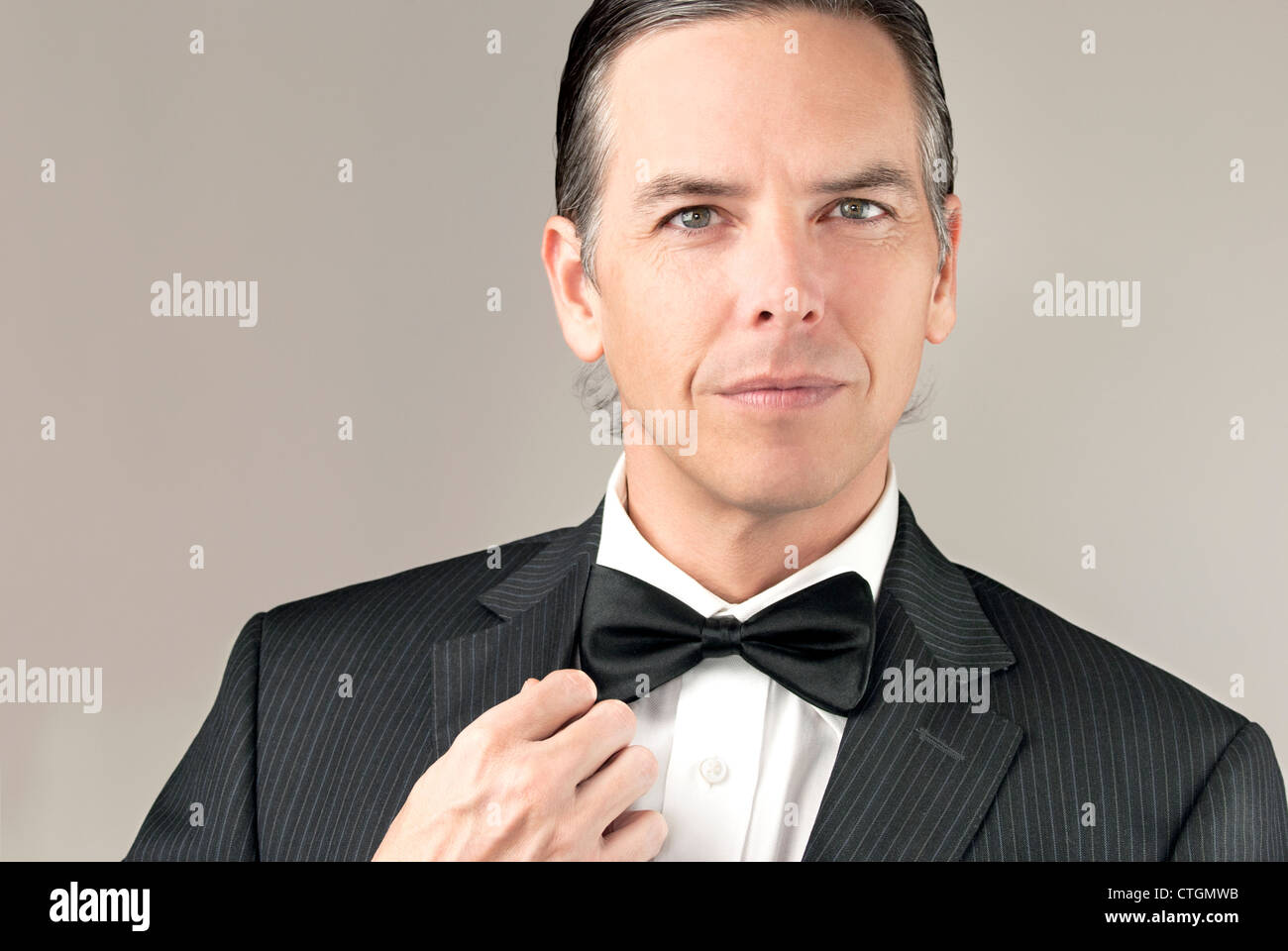 Close-up of a confident gentleman in a tux adjusting his cuff. - Stock Image
