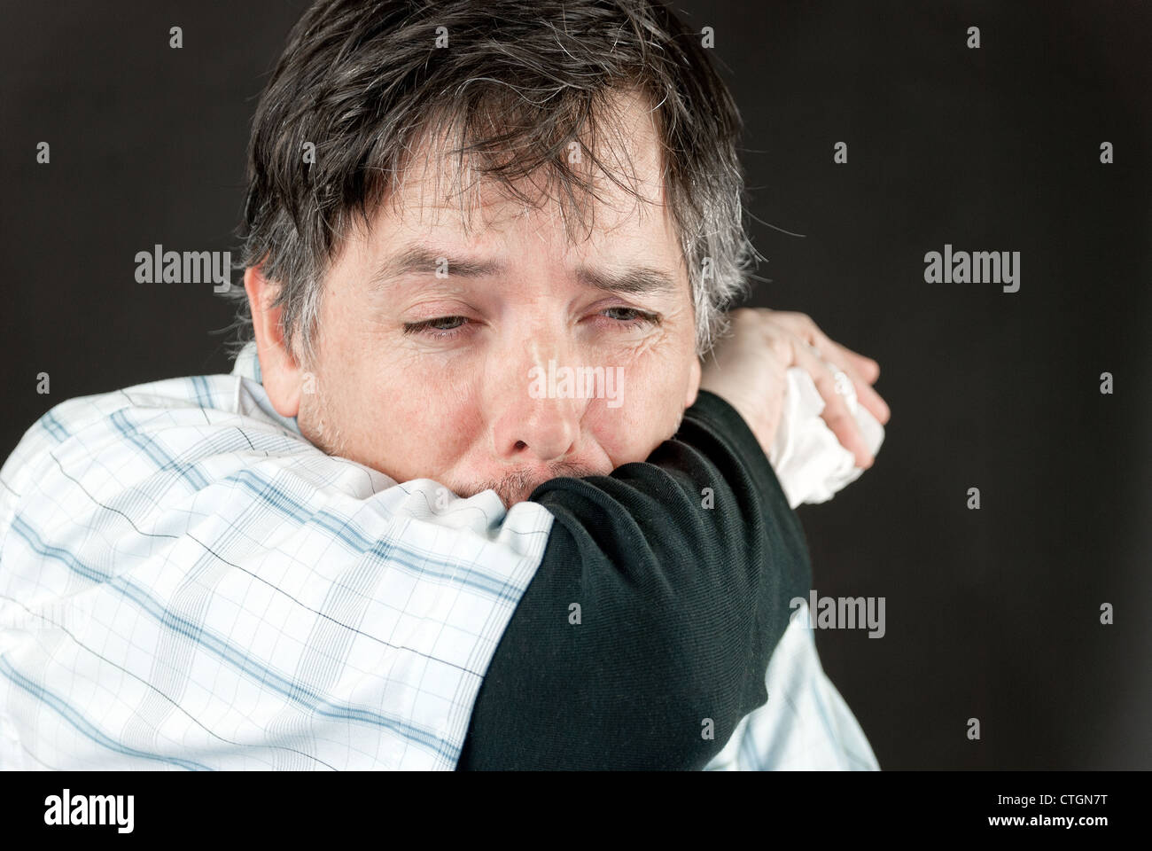 Close-up of a man stifling a sneeze in his elbow. - Stock Image