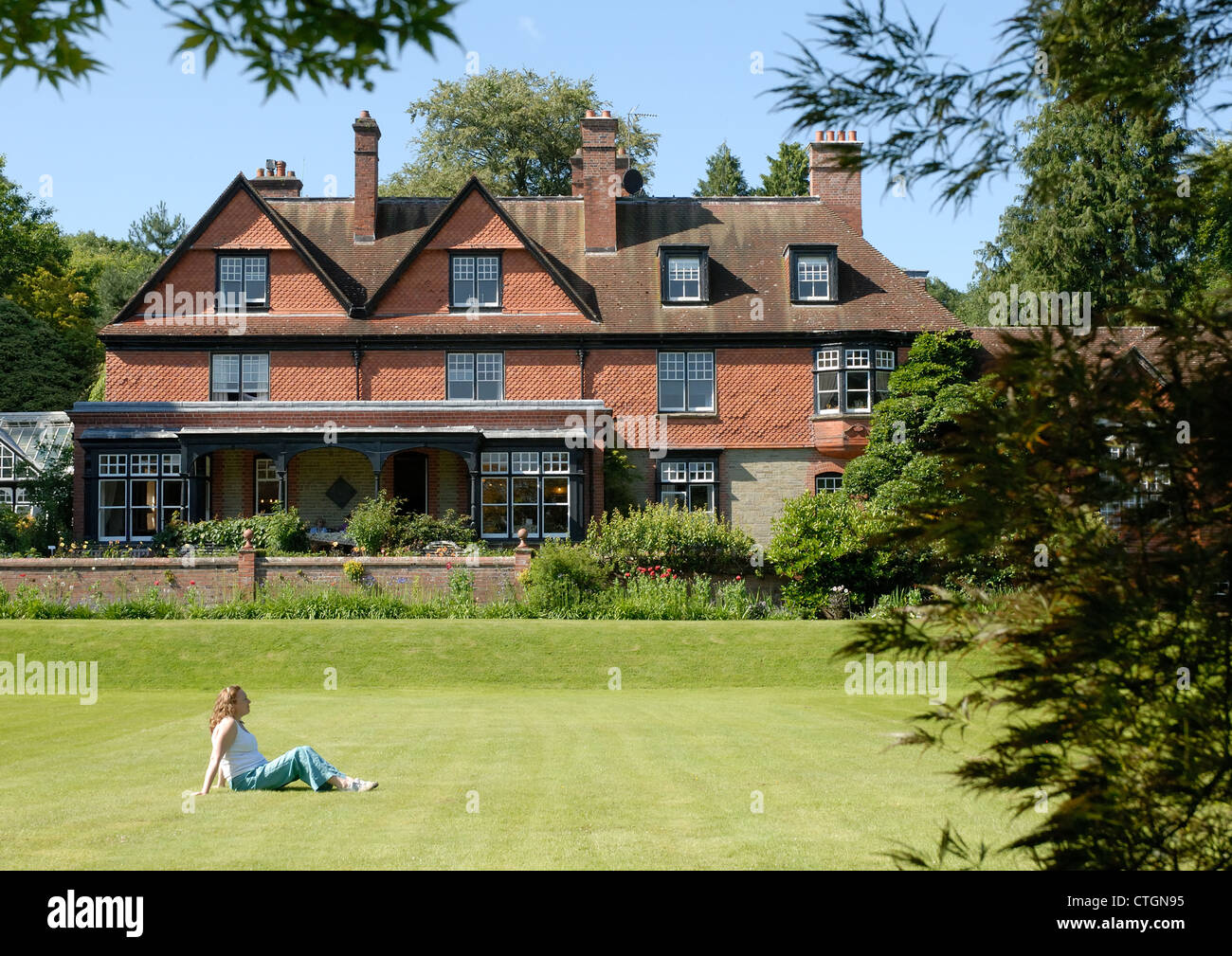 A woman relaxes in the grounds of Hergest Croft Gardens, Kington, Herefordshire. - Stock Image