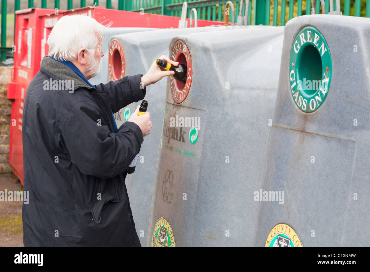 Dunmanyway, County Cork, Ireland. Elderly man dropping bottles into bottle bank at recycling centre. - Stock Image