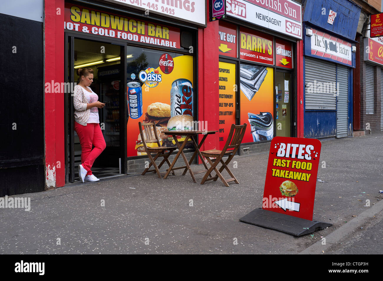 Proprietor of a small sandwich bar and carryout coffee shop with a small pavement table, Govan Road, Govan, Glasgow, - Stock Image