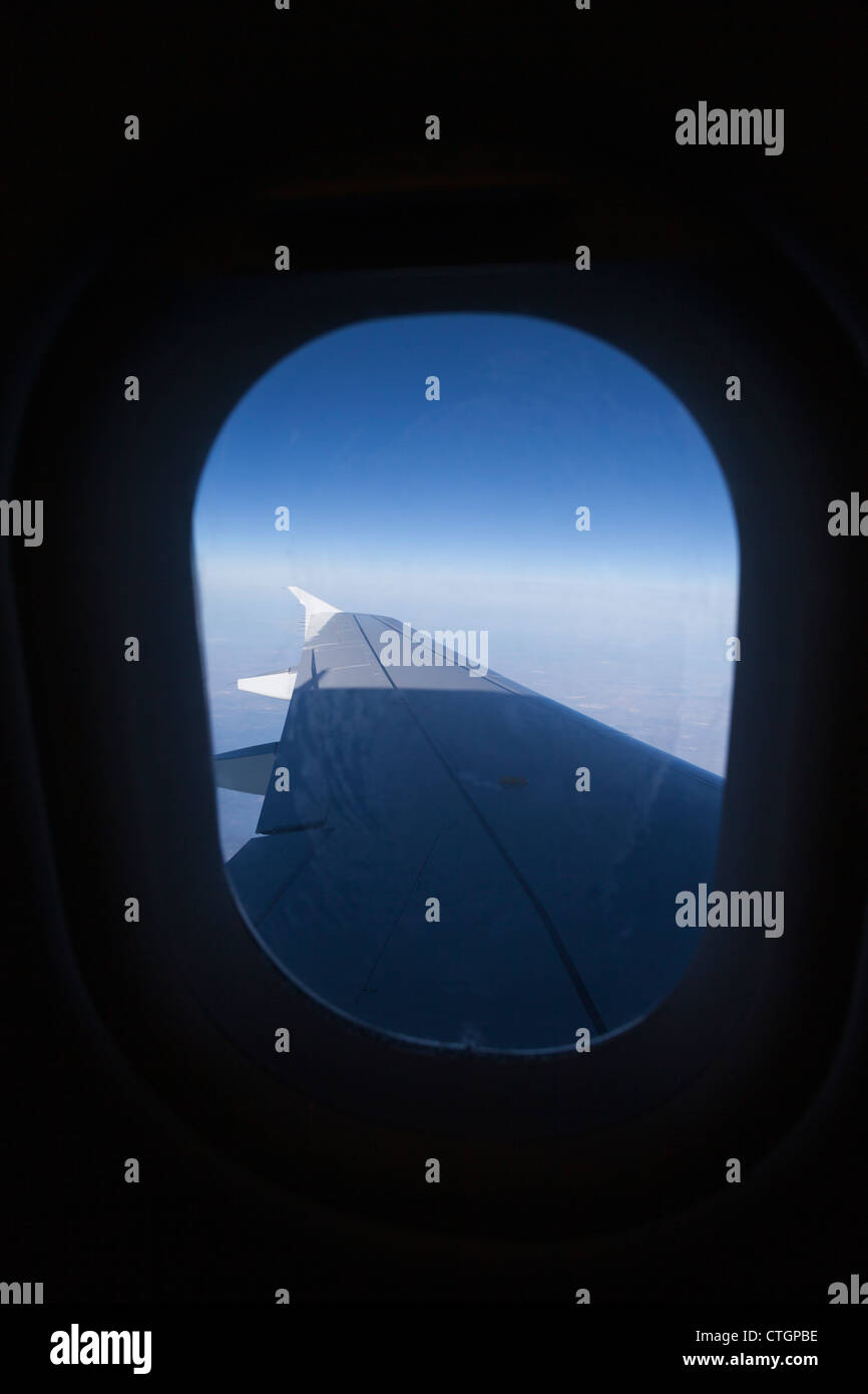 Looking through window of Airbus A320 aircraft to wing. - Stock Image