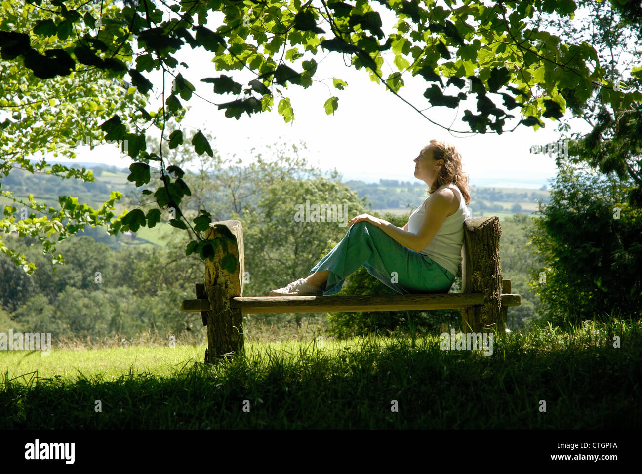 A woman enjoys the sunshine at Hergest Croft Gardens, Kington, Herefordshire. - Stock Image