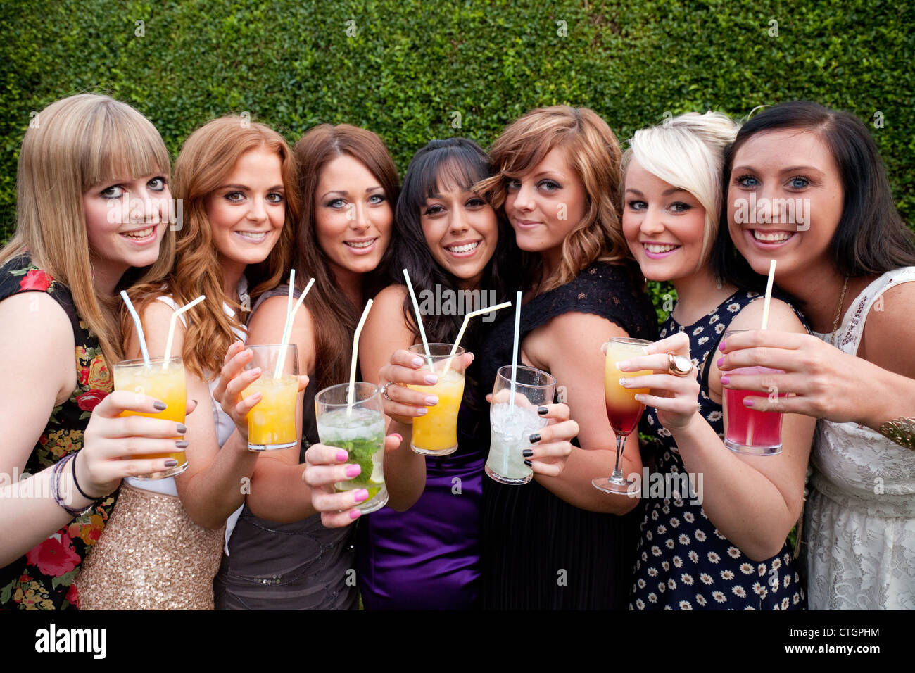 A group of seven young women enjoying drinking alcohol cocktails at a party, UK - Stock Image