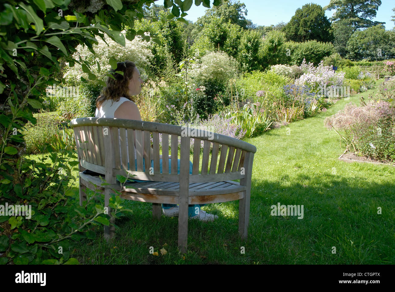 A woman relaxes in a seat at Hergest Croft Gardens, Kington, Herefordshire. - Stock Image