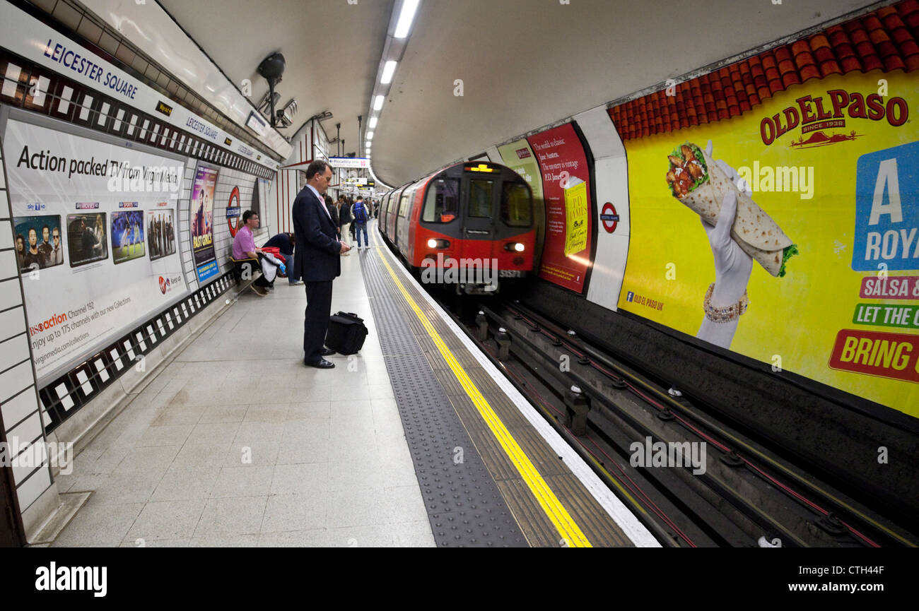 People on the platform waiting for approaching train, Leicester Square Underground Station, London, England, UK - Stock Image