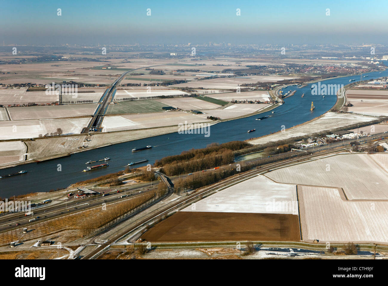 The Netherlands, Willemsdorp, near Dordrecht, Cargo ships in river called Dordtse Kil and A16 highway. Winter. Frost. - Stock Image
