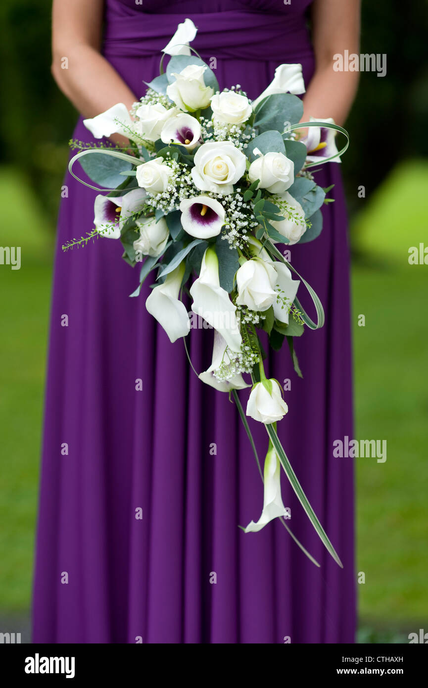 single bridesmaid in a purple dress holding a wedding bouquet Stock ...