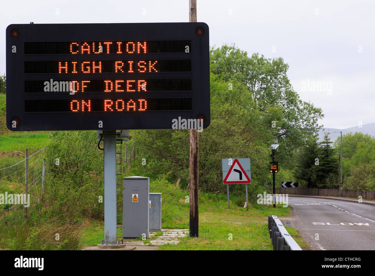 Matrix sign on A85 warning 'take caution high risk of deer on road' with slow before bend and high fence - Stock Image