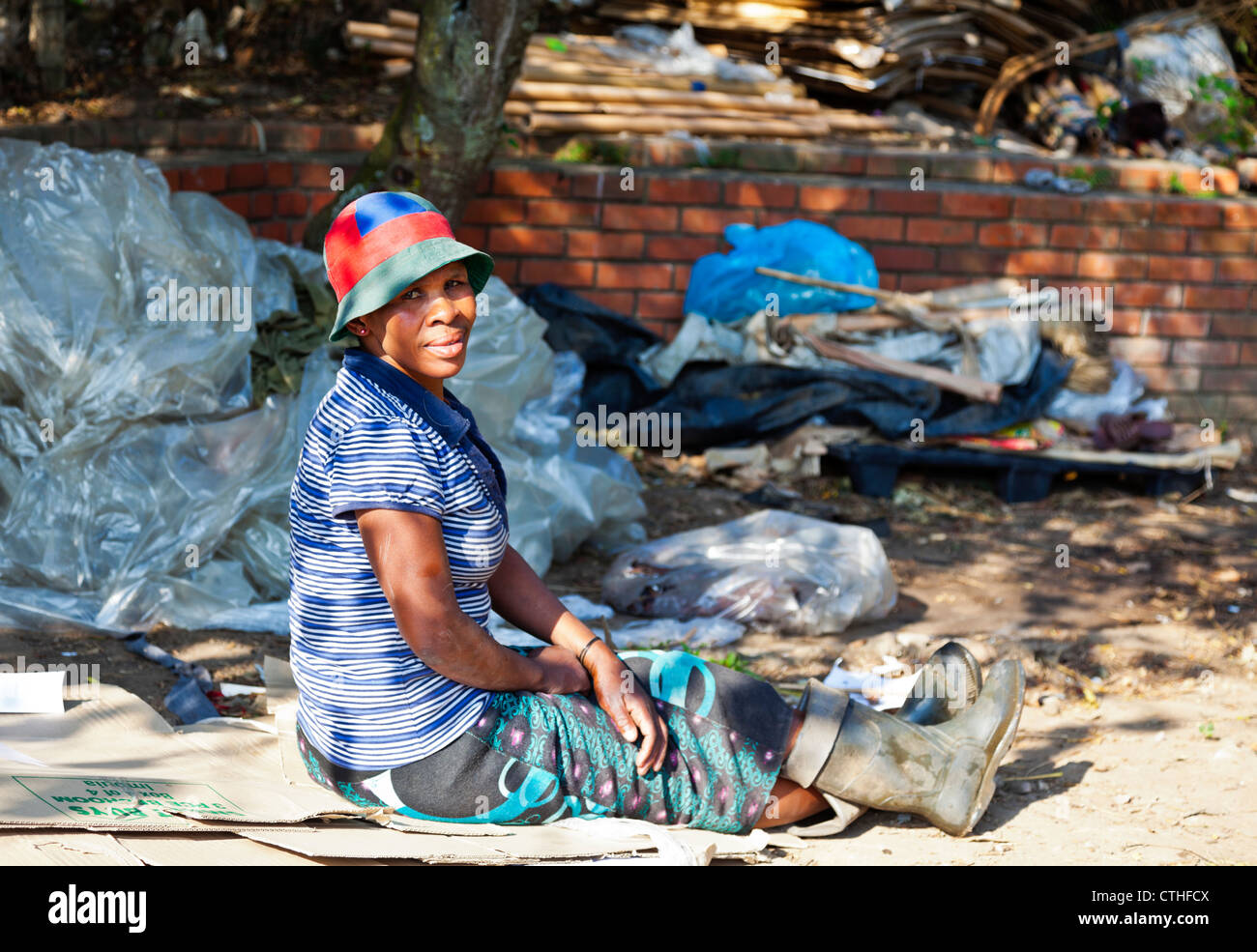 The plight of the poor in Africa as this African woman is forced to live and work in the streets of a city in South - Stock Image