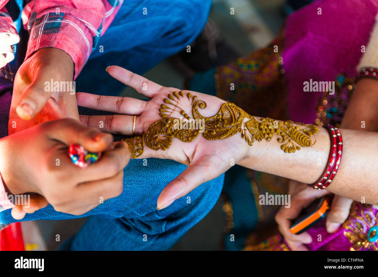 An Indian woman gets henna tattoos on the hands, India - Stock Image