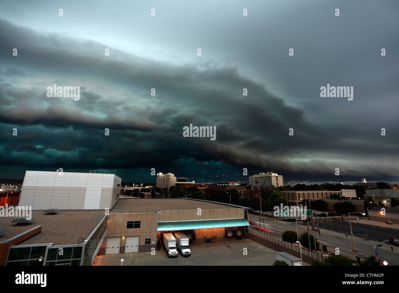 Highly detailed shelf cloud thunderstorm, showing marked green color and cloud layer delineation over a city. - Stock Image
