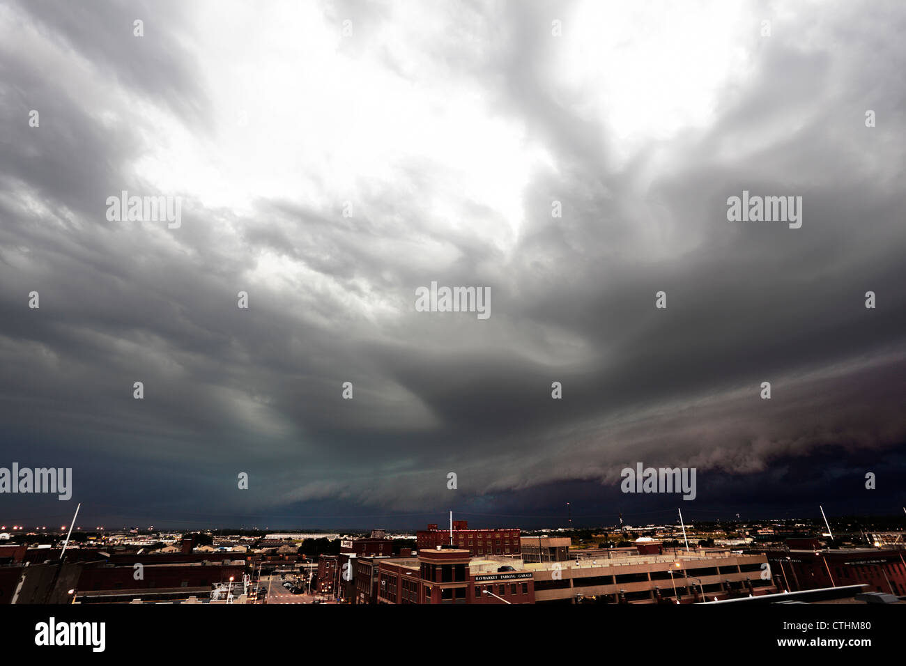 A squall line thunderstorm flies over a city, with distinct outflow areas visible on top. - Stock Image