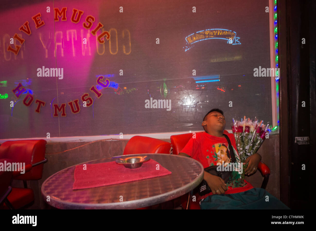 street trader, child with flowers sleeping in front of Nightclub, Soi Cowboy, nightlife center, bars, Bangkok, Thailand - Stock Image