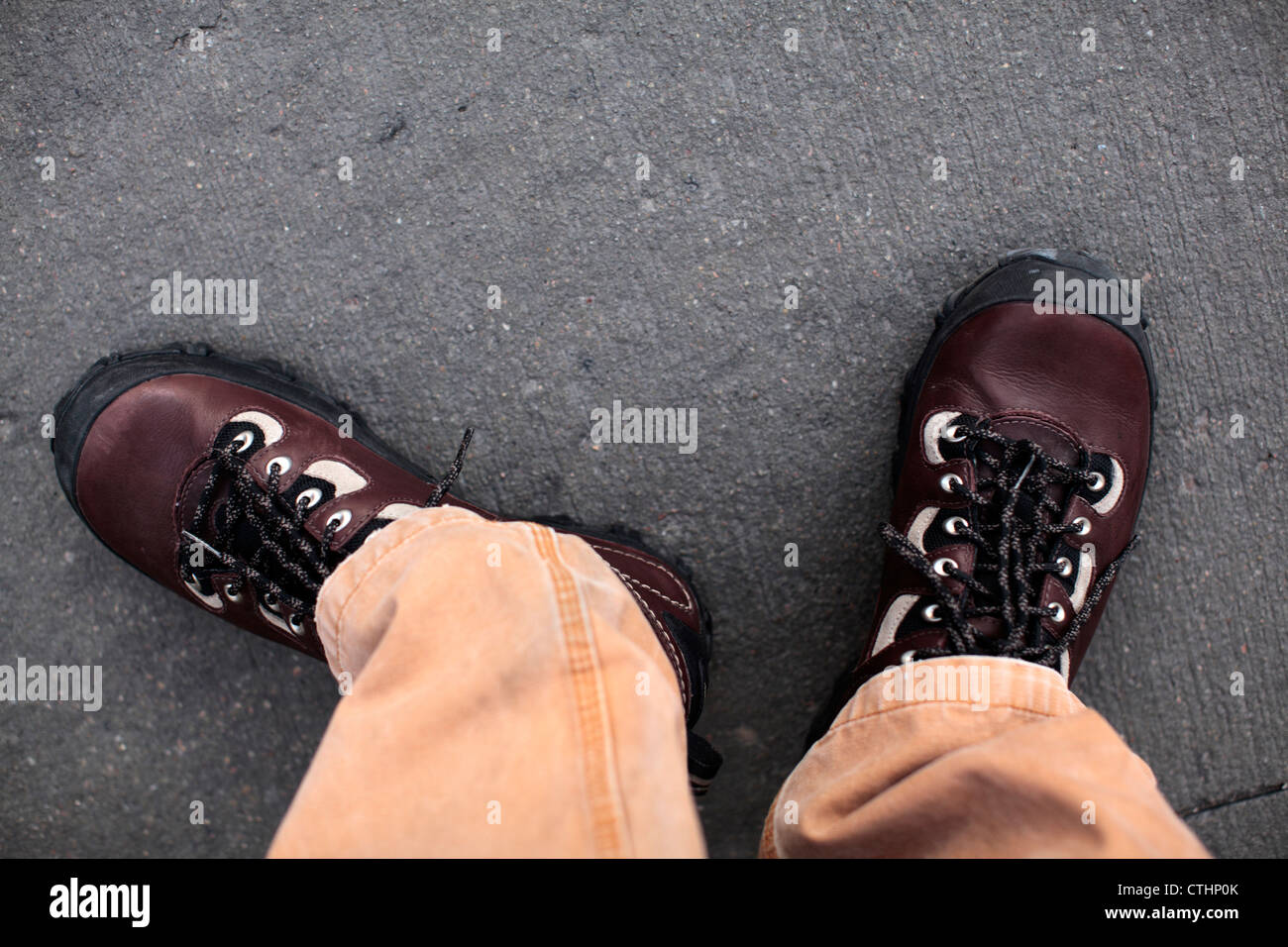 Male feet wearing brown leather Patagonia Drifter shoes and canvas khaki pants. - Stock Image