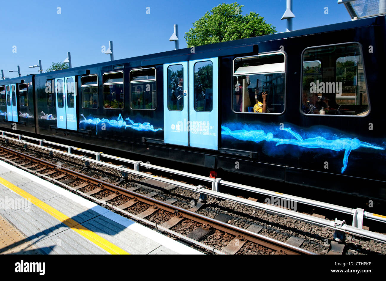 DLR train branded with 'scanned' swimmers by GE for Olympics, London - Stock Image