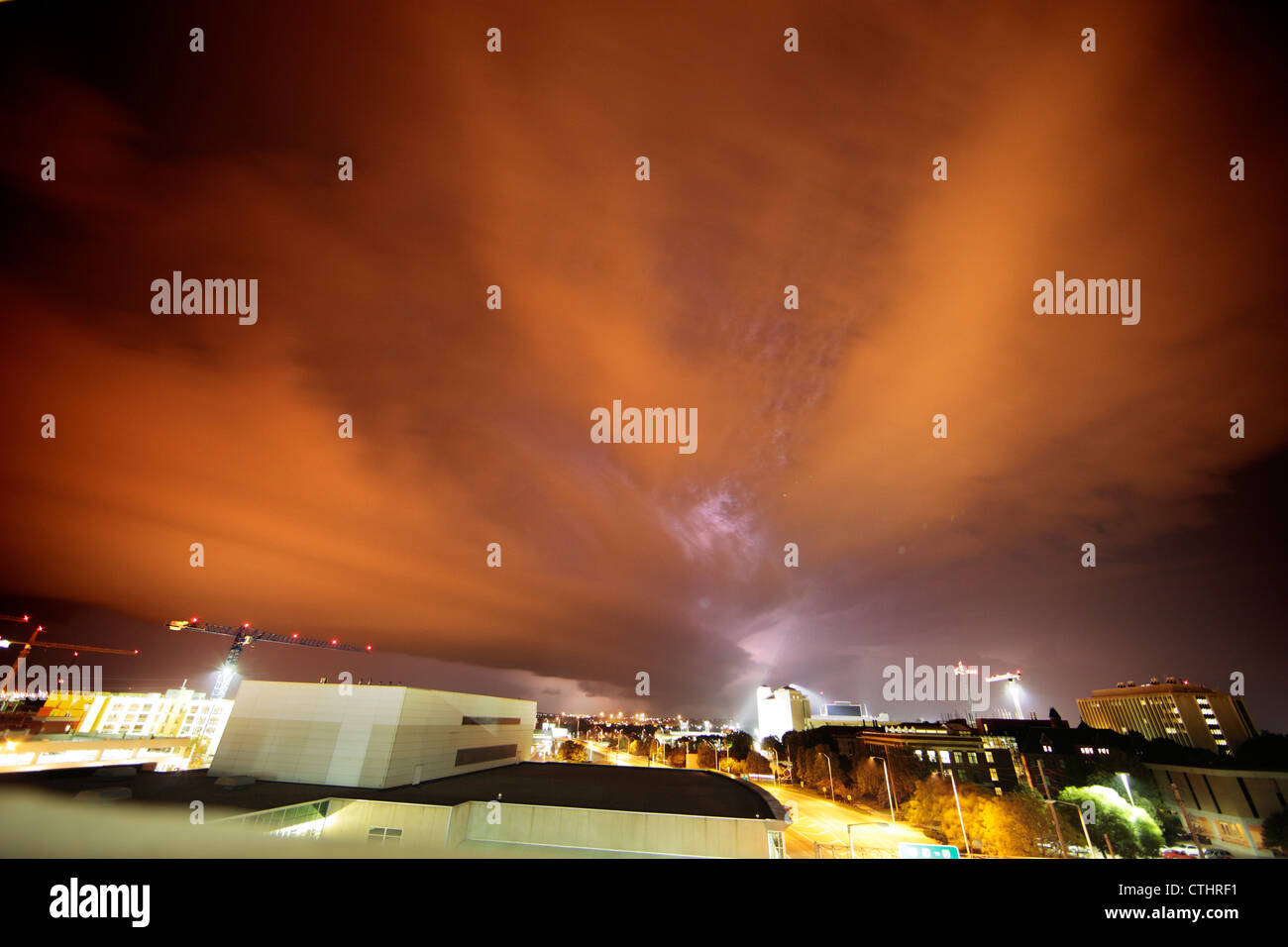 Shelf cloud, lit reddish orange by city lights, passes over a city as lightning strikes behind. - Stock Image