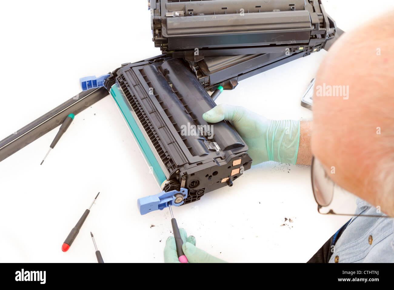 worker Laser printer on a workbench. Printer workshop - Stock Image