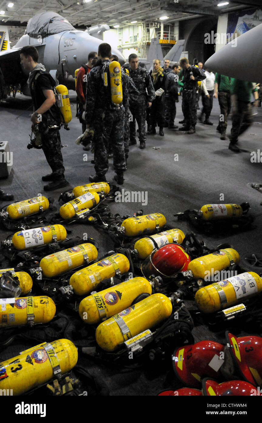 Sailors stand by to recharge their self-contained breathing apparatus (SCBA) in the hangar bay of the aircraft carrier - Stock Image