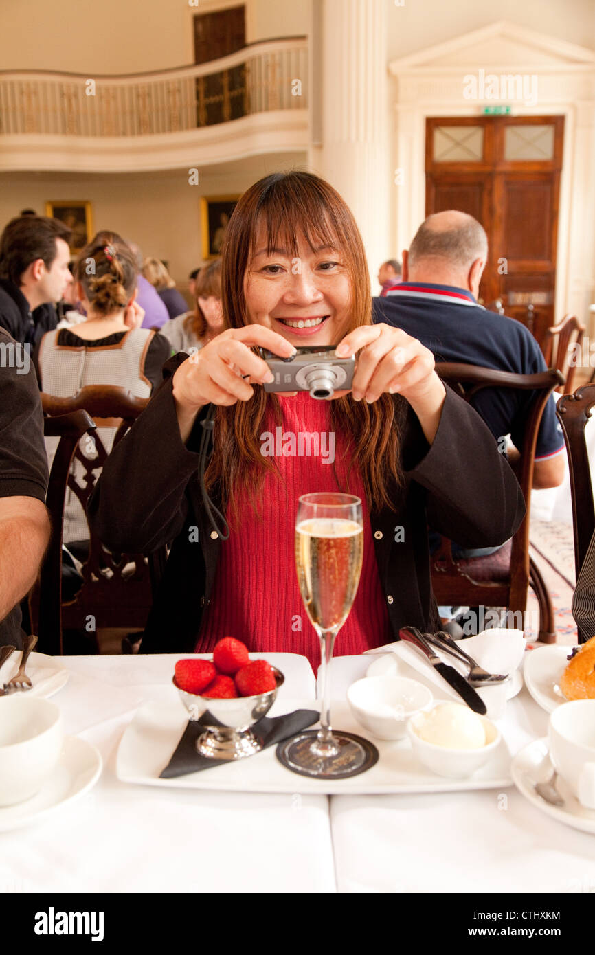 Asian tourist taking a photo of afternoon tea and champagne, Bath Pump room tearooms restaurant, Somerset UK Stock Photo