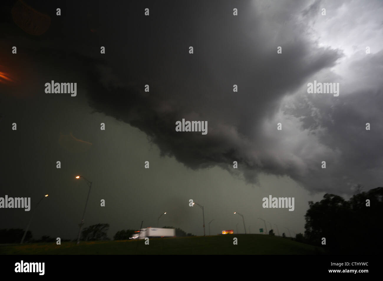 The front edge of a squall line thunderstorm opening up showing green background above highway. - Stock Image