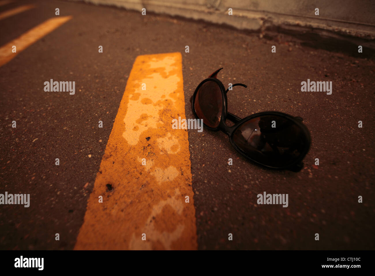 Lit by unearthly orange light from a storm which wet the paving, a pair of sunglasses next to a parking stripe. - Stock Image