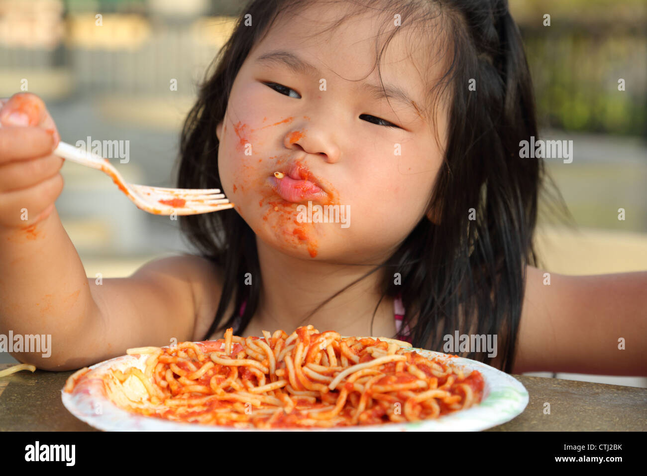 Young girl eating spaghetti and making mess - Stock Image