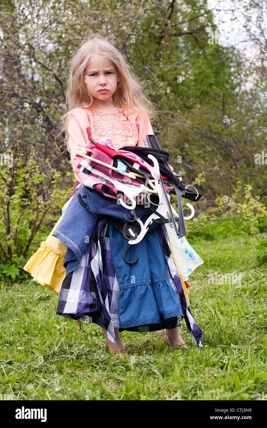 sad little girl standing with heap of dresses in her hands - Stock Image