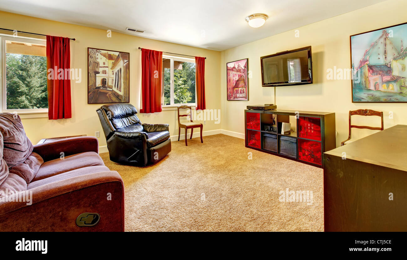 Tv living room with art and red curtains and beige carpet with brown furniture. Stock Photo
