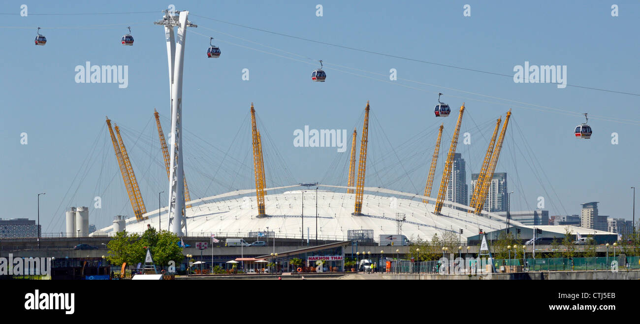 Emirates Air Line cable cars seen in front of The O2 arena dome viewed from Royal Docks crossing River Thames linking - Stock Image
