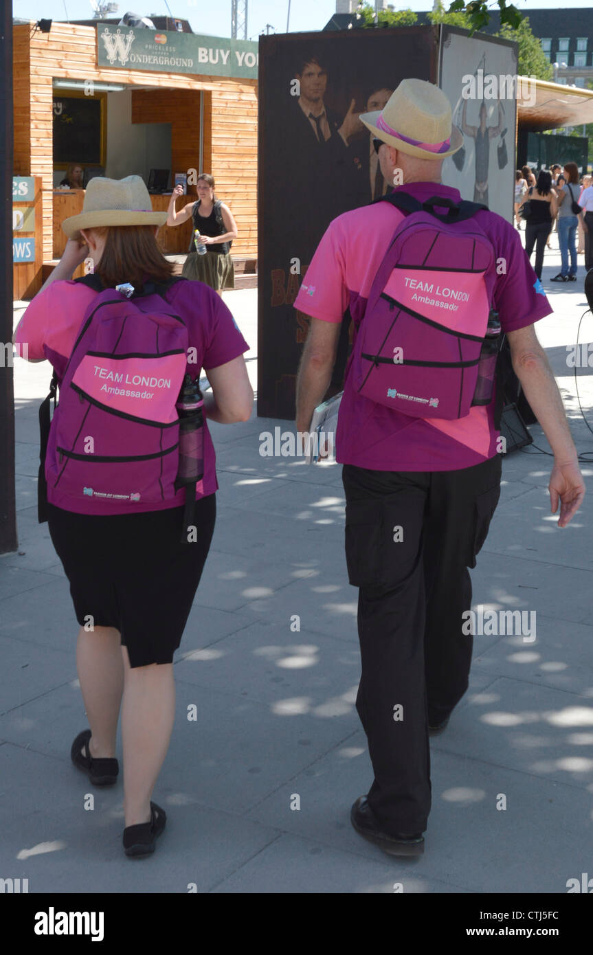 Two Games Makers also known as Team London Ambassadors (helpers) in 2012 London Olympic uniforms walking along near Stock Photo