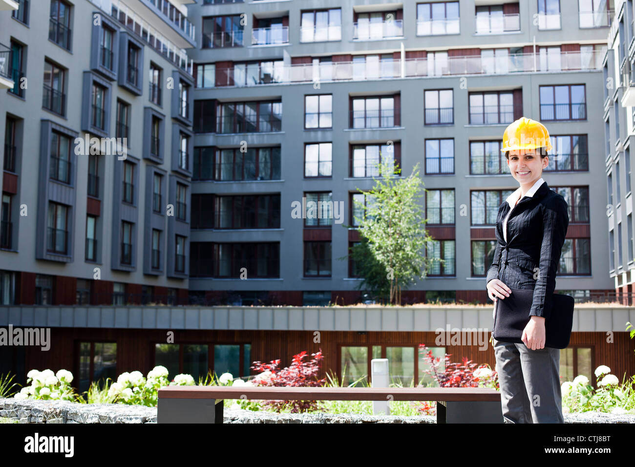 Female construction engineer and yellow helmet - Stock Image