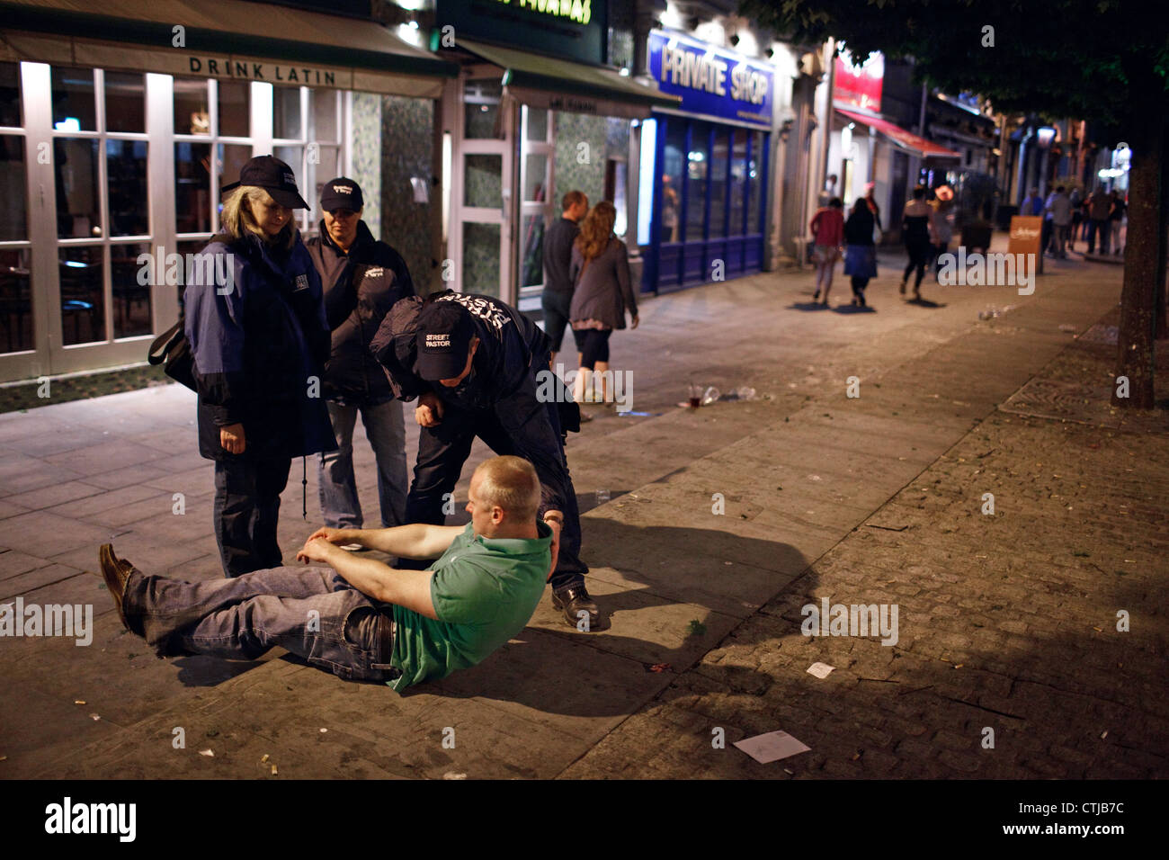 Street Pastors help a drunk young man on a Saturday night in the city centre of Cardiff, Wales, Great Britain (UK). - Stock Image