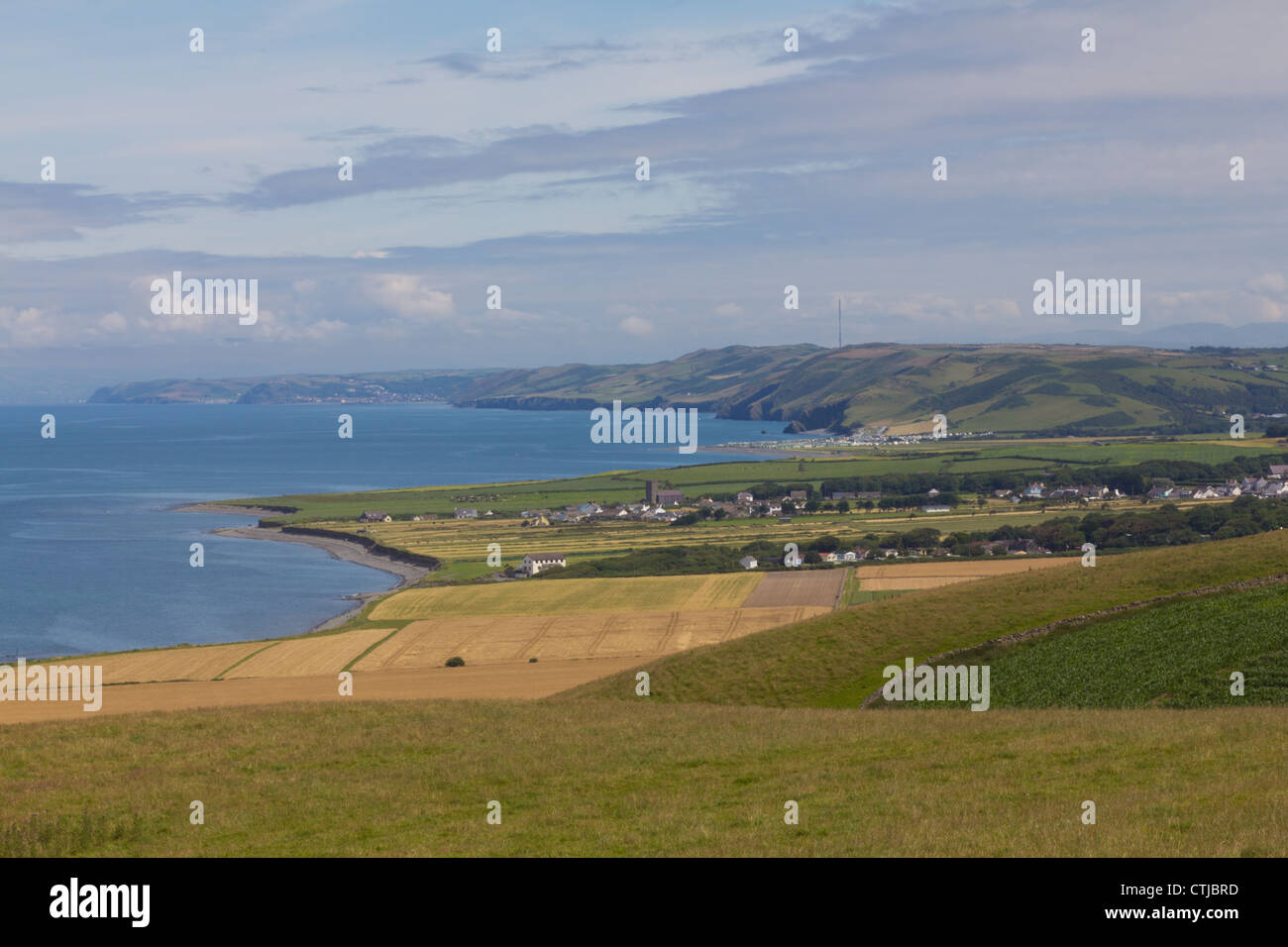 Sunny view of the Cardigan Bay, on the Welsh coast towards Llanon and Aberystwyth and Snowdonia in the far distance. - Stock Image