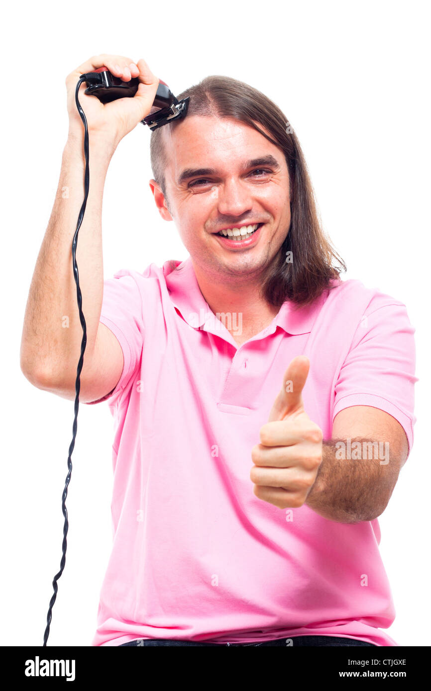 Happy young man shaving his head with hair trimmer, isolated on white background. - Stock Image
