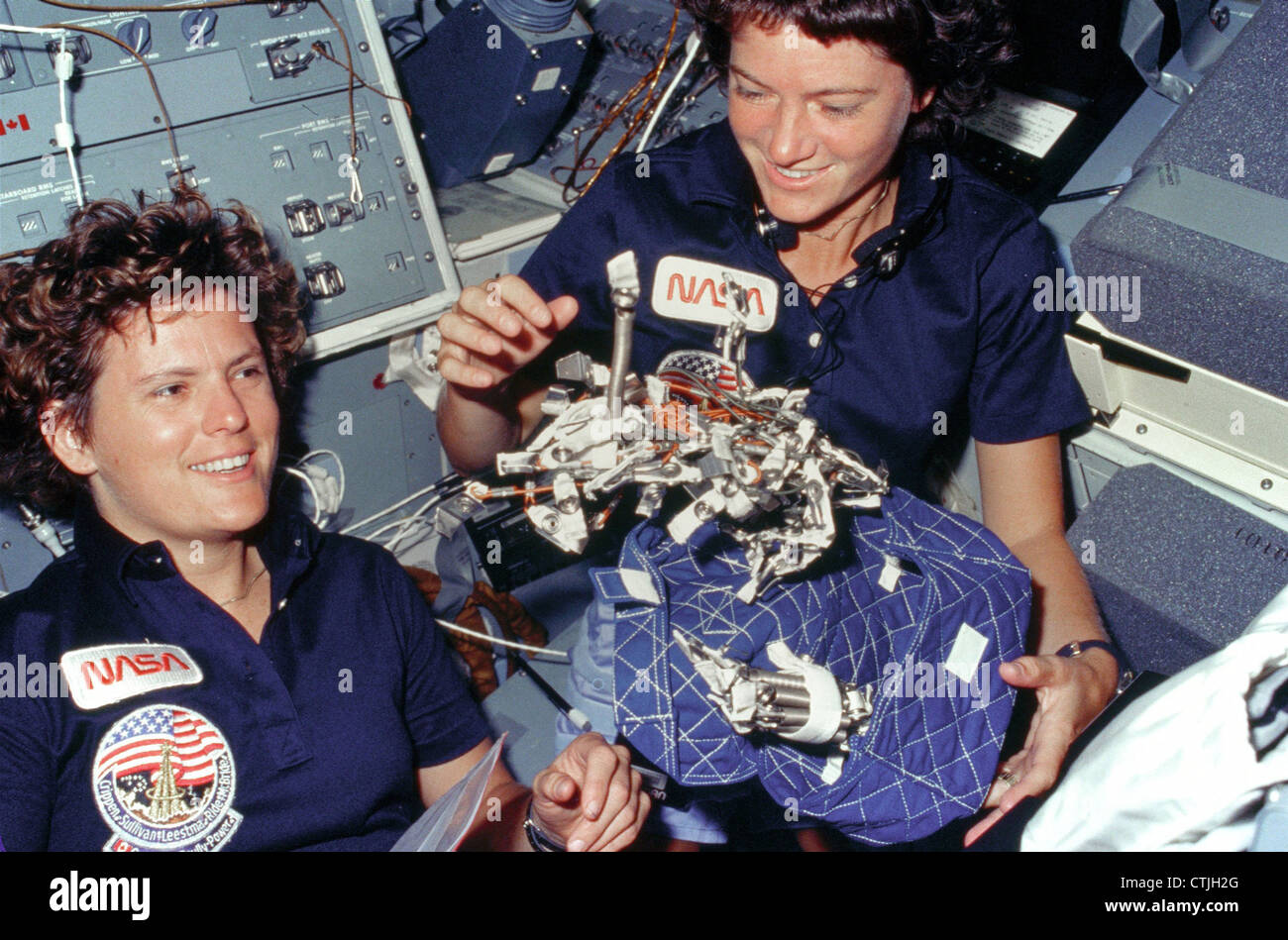 Astronauts Kathryn D. Sullivan, left, and Sally K. Ride display a sleep restraint used aboard the space shuttle - Stock Image