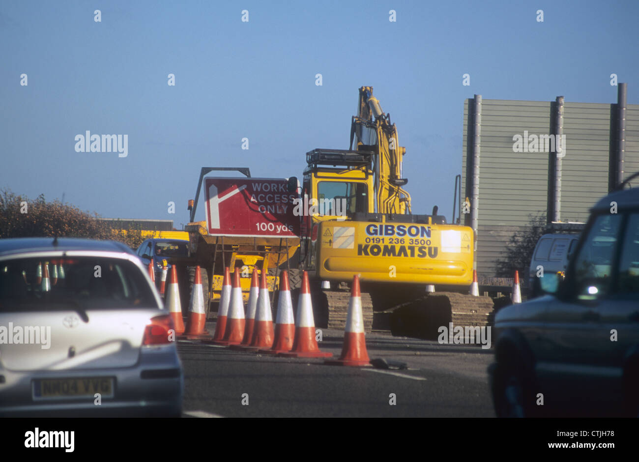 A Komatsu Excavator employed upon a road re-surfacing project in Northern England, as traffic is directed by feeder - Stock Image