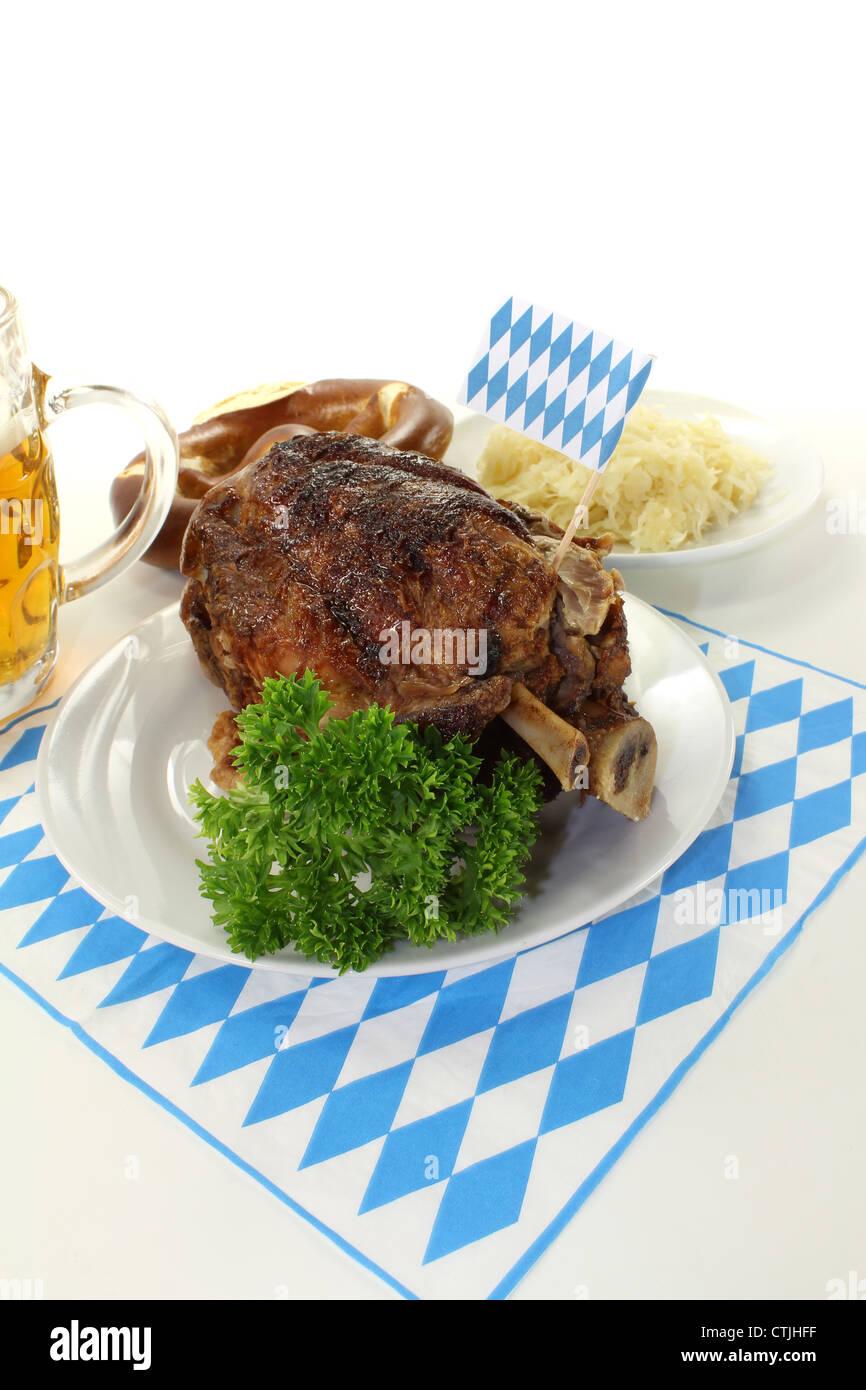 Bavarian roasted pork knuckle and pretzels with sauerkraut on a light background - Stock Image